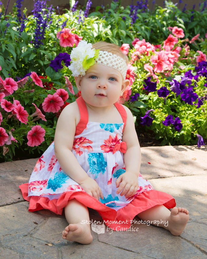 One year old girl sitting among flowers