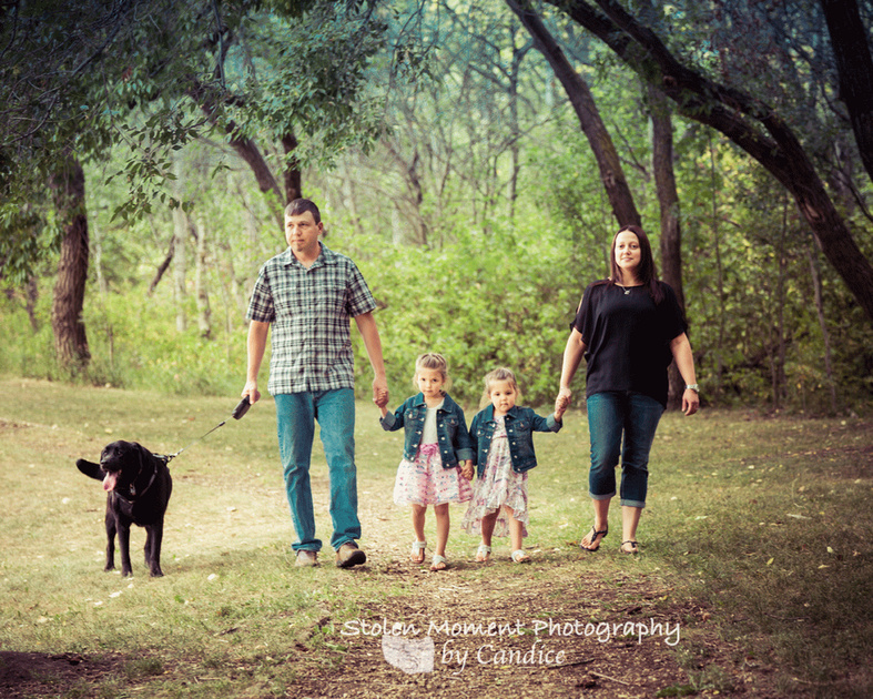 family of four walking toward camera with their dog