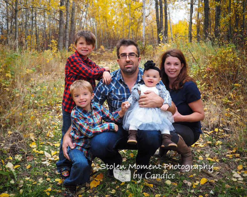 Family of five posed in the fall leaves