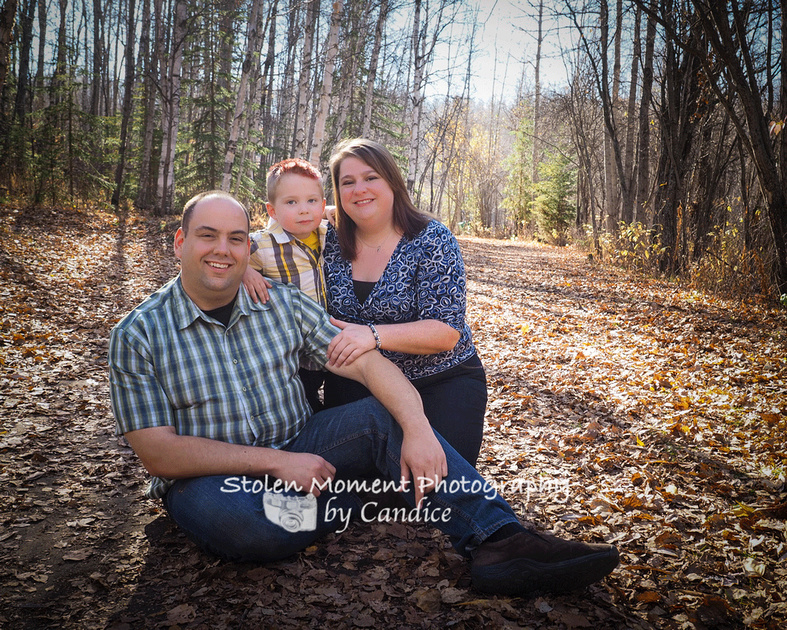 mom, dad and son posed among the fall leaves