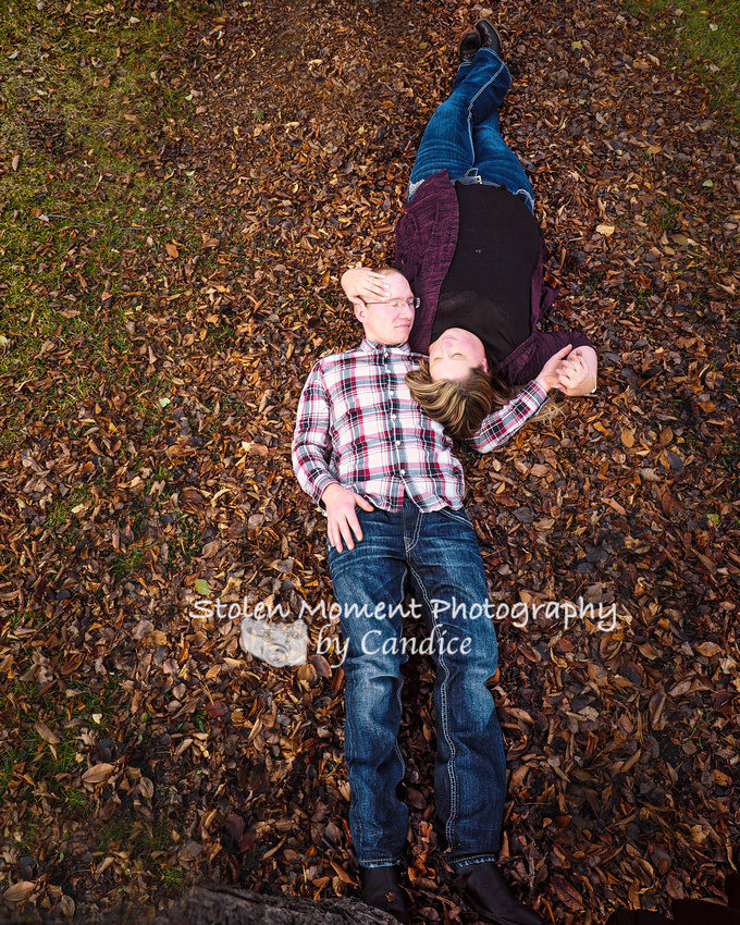 engaged couple laying in the fall leaves