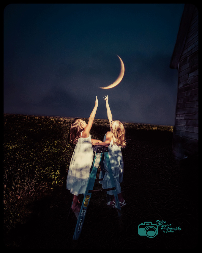 two girls standing on ladder in field reaching for the moon