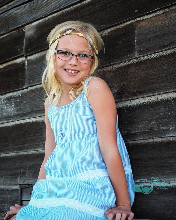girl in sundress sitting outside old barn