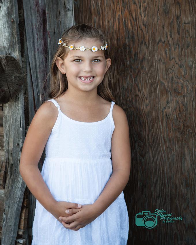 girl in white sundress standing outside a barn