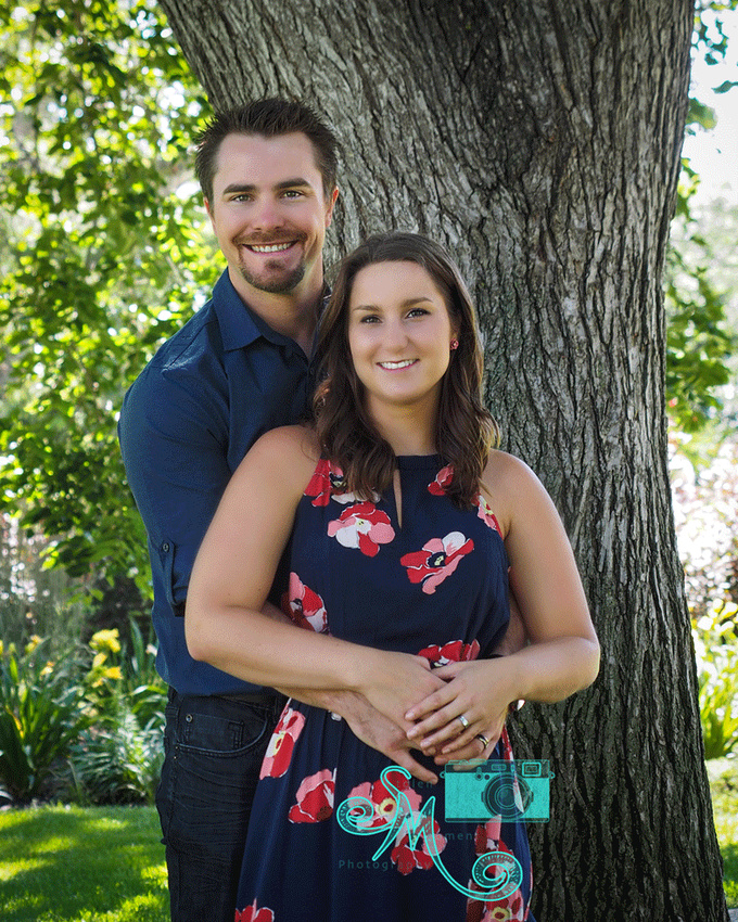 couple pose in front of tree
