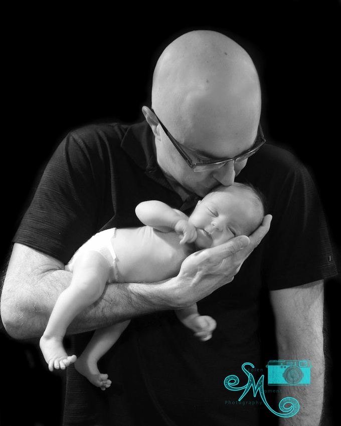 A dad holding his newborn daughter, leans down to place a kiss on her head