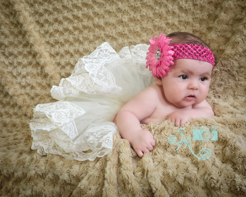 baby in tutu with flower headband laying on her tummy