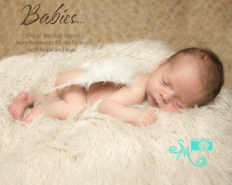 a newborn boy sleeping with angel wings on his back