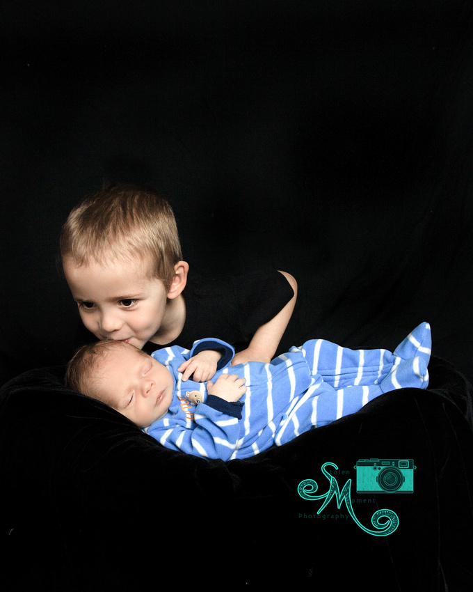 big brother leans over to give a kiss to his newborn brother