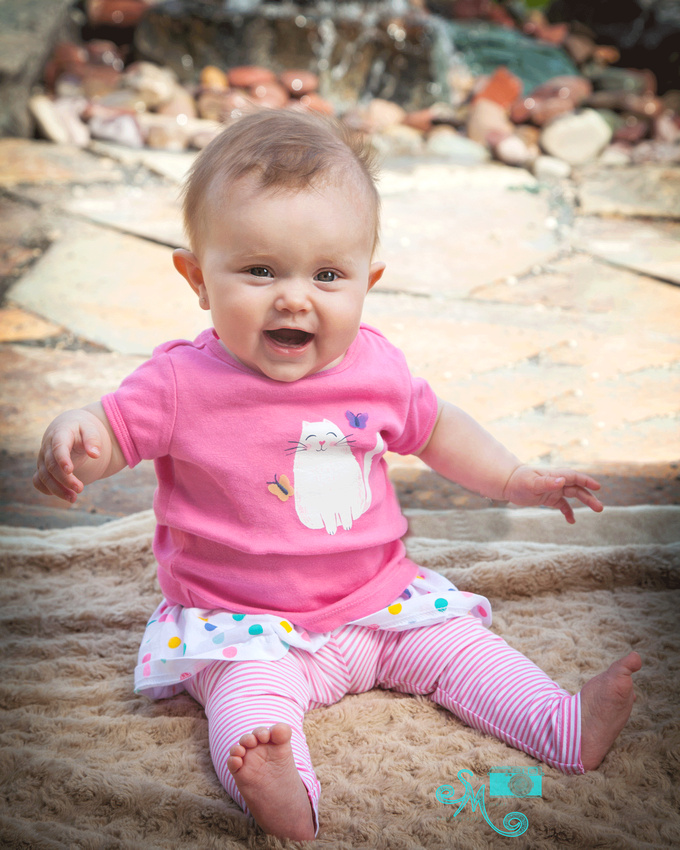 six month old baby girl sitting and smiling at camera