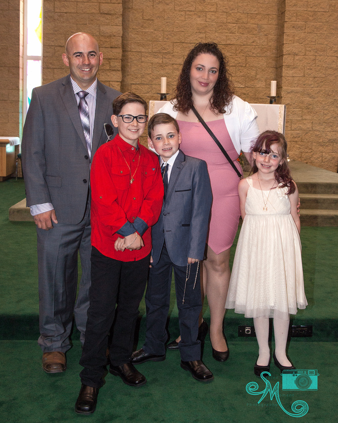 a family poses in front of the alter after First Communion
