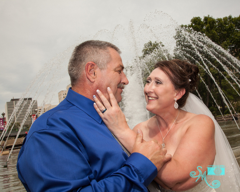 bride caresses grooms cheek with water fountain in behind