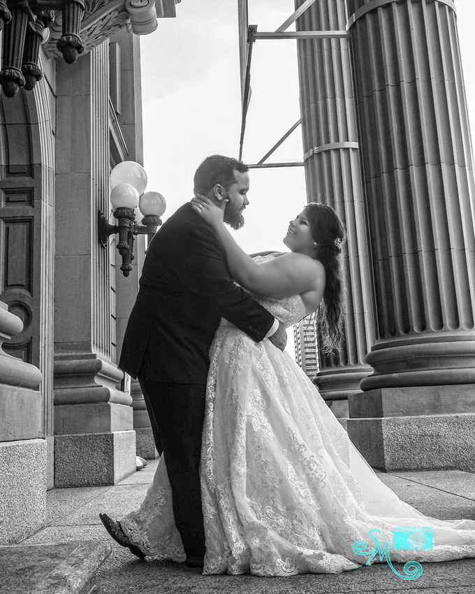 the groom dips his bride on the steps of the legislative building
