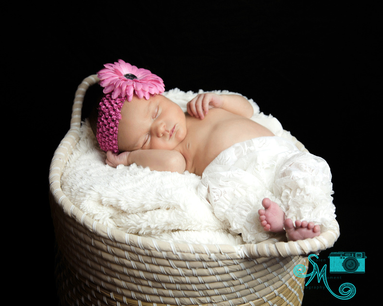 a newborn girl sleeps in a  basket wearing a pink flower on her head and lacy pants