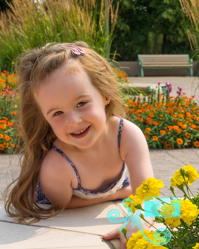 little girl looks up from flowers and smiles for camera