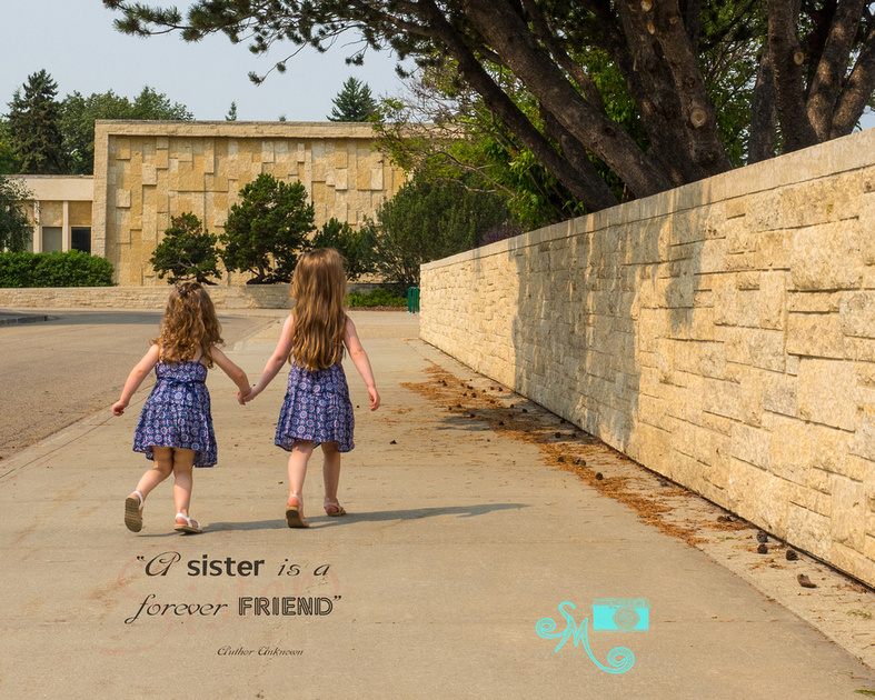 two sisters walk hand in hand on a sidewalk