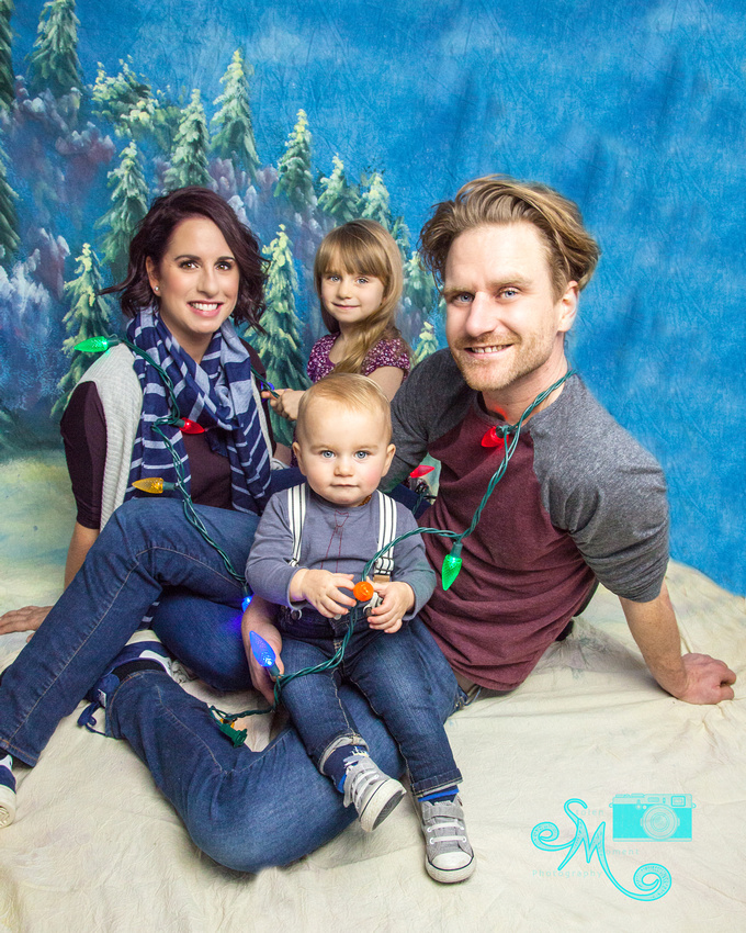 a family of four sit in front of a winter backdrop with Christmas lights draped over them