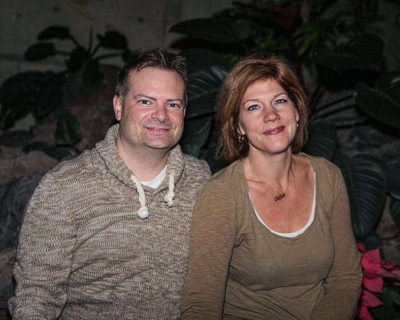 a couple sit in front of greenery in Lee Pavilion at Citadel theatre