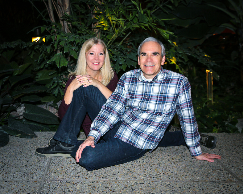 a couple sit on floor in front of greenery at the Lee Pavilion in the Citadel Theatre