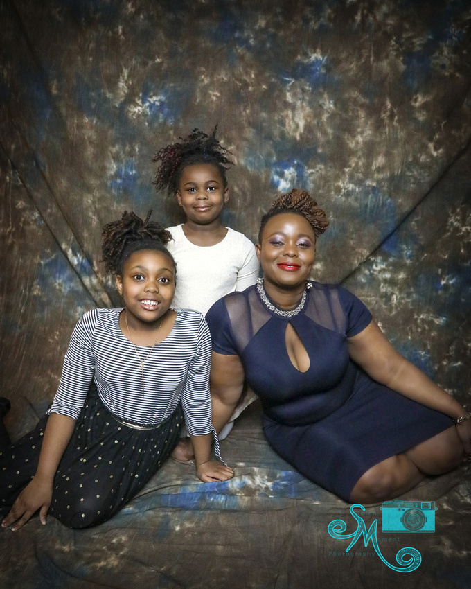a mom and her two daughters pose for the camera