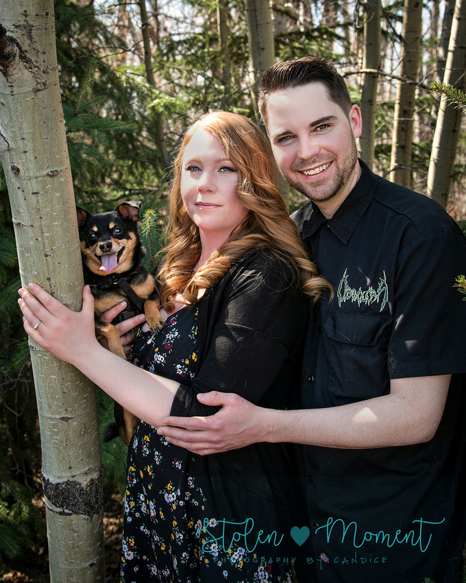 a man holds his fiance in his arms while she holds their little dog while standing next to a tree