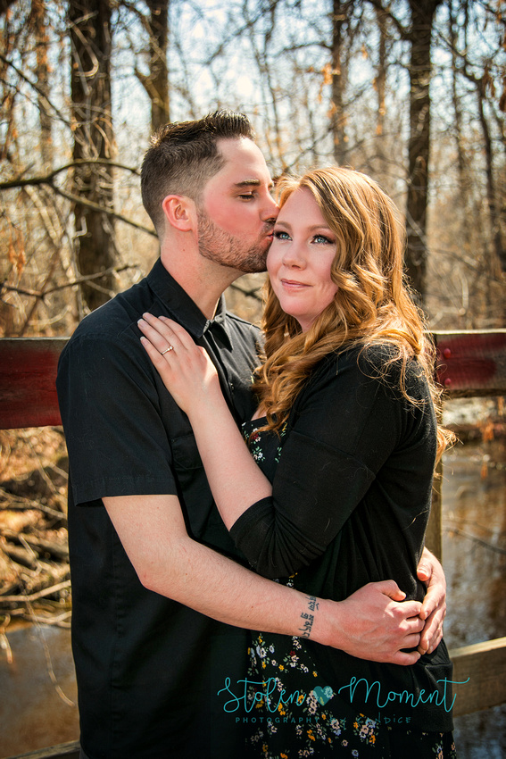 a man kisses his fiance on the temple while standing on a bridge with her smiling off into the distance
