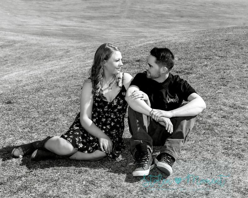 a black and white image of a man and his fiance sitting on a hill looking into each other's eyes