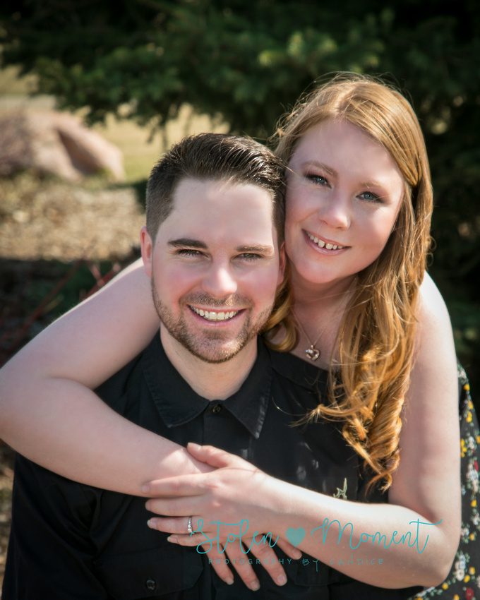 a woman cuddles her fiance around the neck showing off her engagement ring as they both smile for the camera