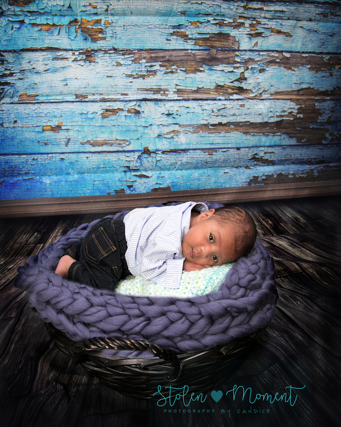 a newborn boy lays on his tummy in a basket in jeans and dress shirt looking at camera