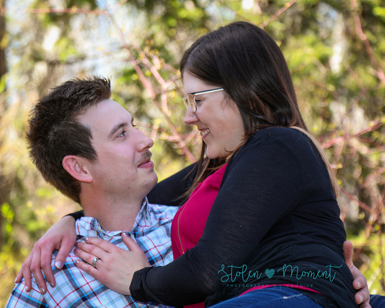 a man and his fiance smile into each others eyes while sitting in the park