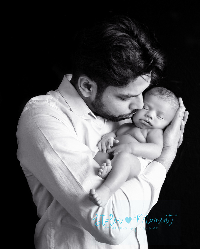 a dad kisses the cheek of his sleeping newborn son while holding him in his arms
