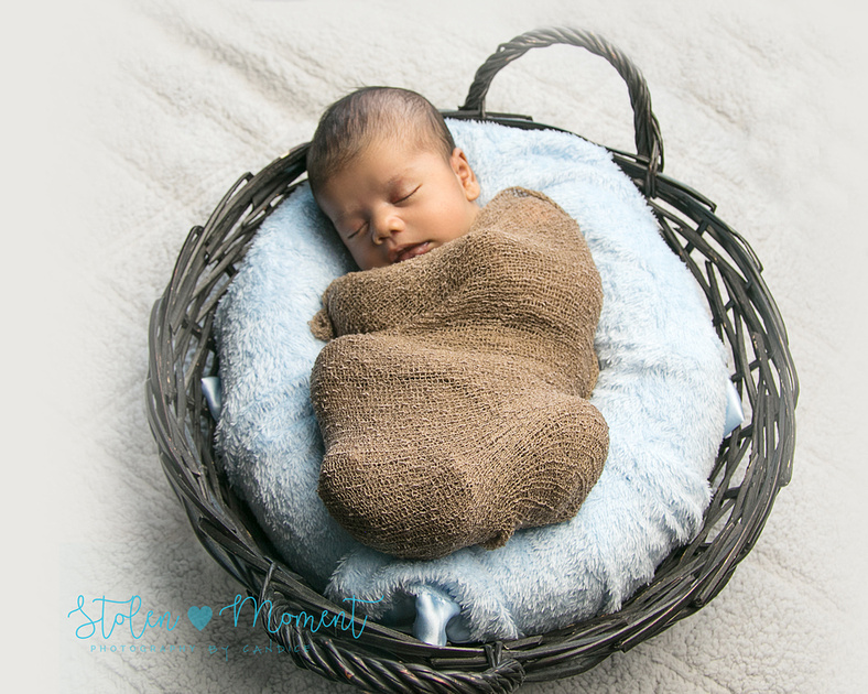 a baby sleeps peacefully while wrapped in a blanket and laying in a  basket