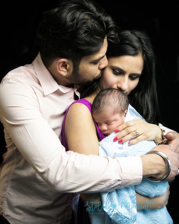 a dad holds his wife and kisses her cheek while she cradles their son and kisses his head