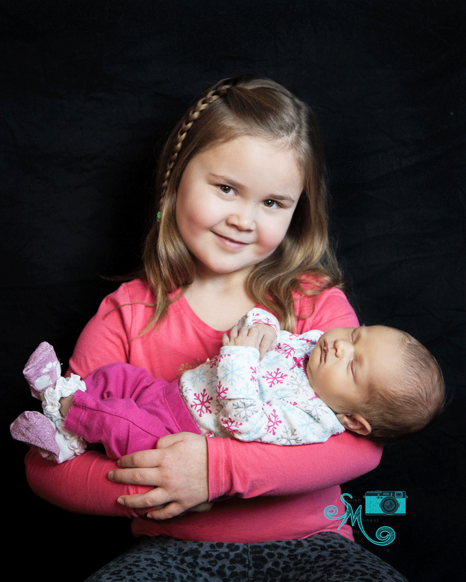 a little girl holds her newborn sister in her ams and smiles at camera