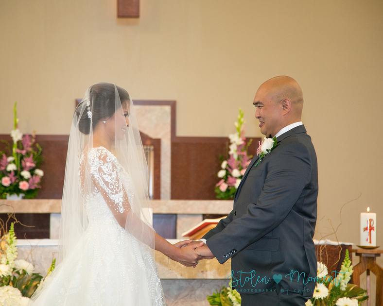 the bride and groom at the alter holding hands smile at each other