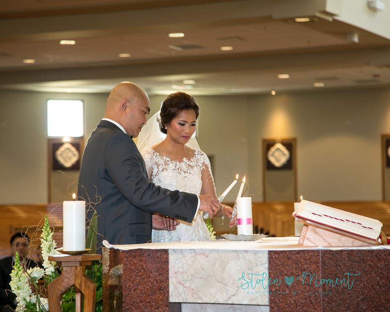 the bride and groom light a candle on the alter at Corpus Christi church