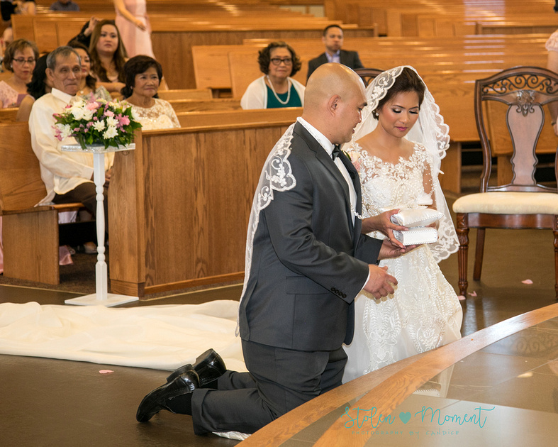 the bride and groom on their knees at the alter during a traditional Filipino veil, cord and bible ceremony