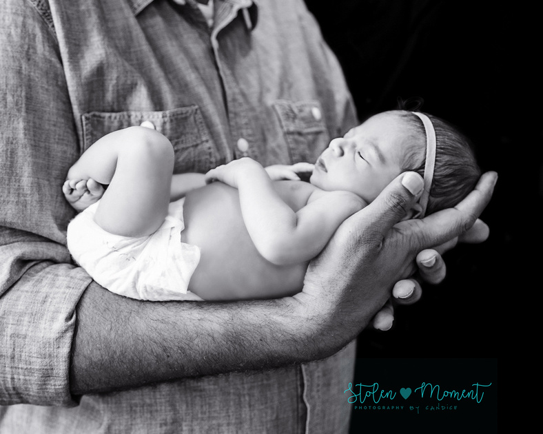 A newborn girl sleeps while cradled in her daddy's arm