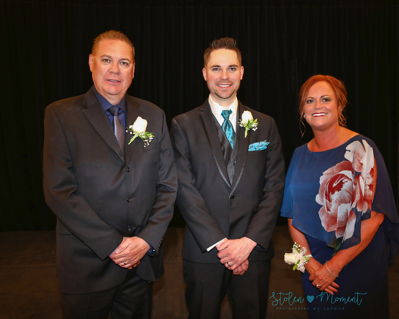 The groom stands with his father and step mother