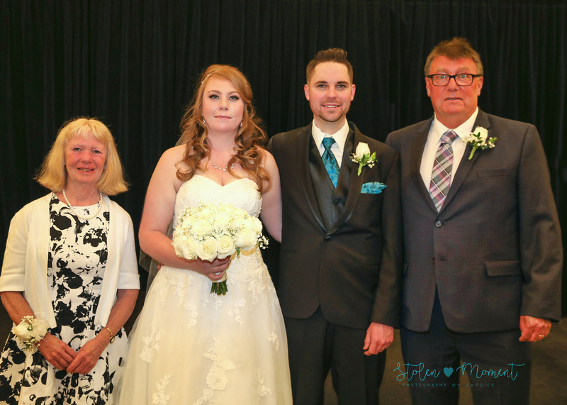 the bride and groom stand between the bride's mom and dad