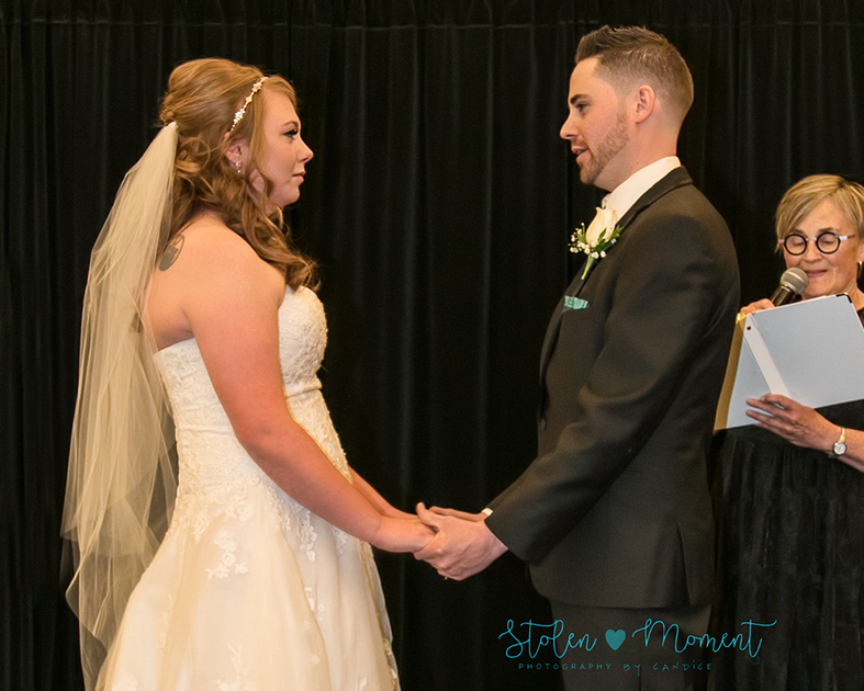 the bride and groom hold hands at alter and say their vows