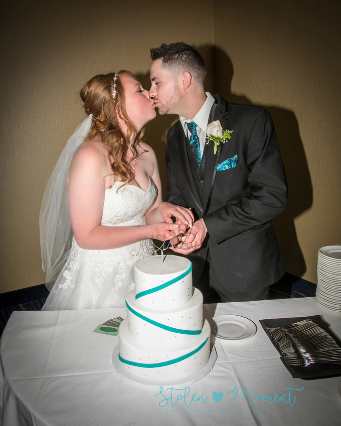the bride and groom share a kiss before cutting the wedding cake
