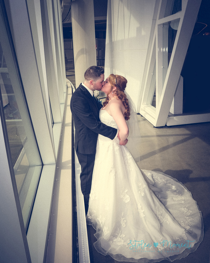 the bride and groom share a kiss by some of the windows at Roger's place