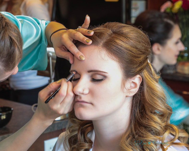 the bride getting her makeup done
