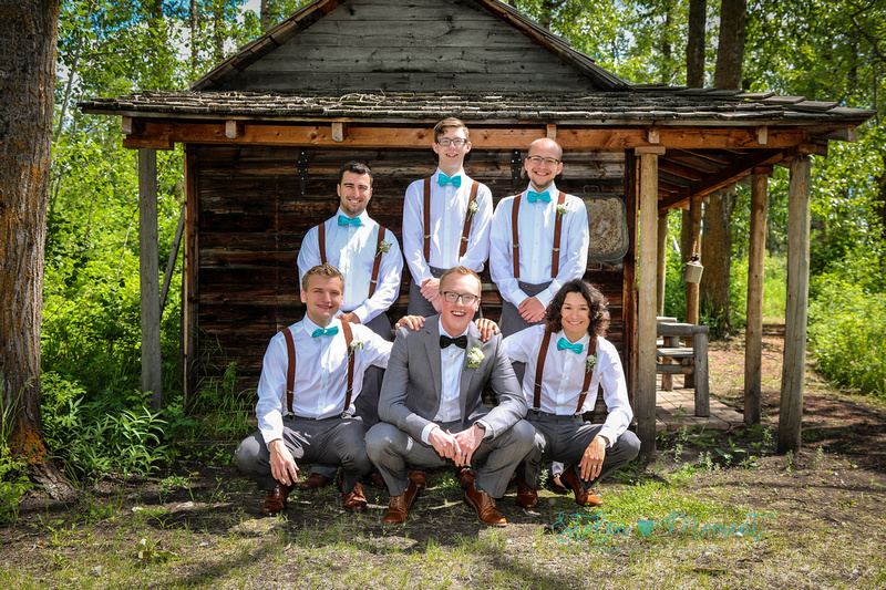 the groom squats down with two of his groomsmen while three others stand behind him with a old wooden shed in the background