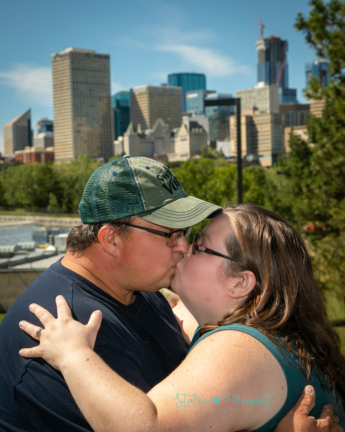 an engaged couple kiss in the foreground with the downtown skyline in the background