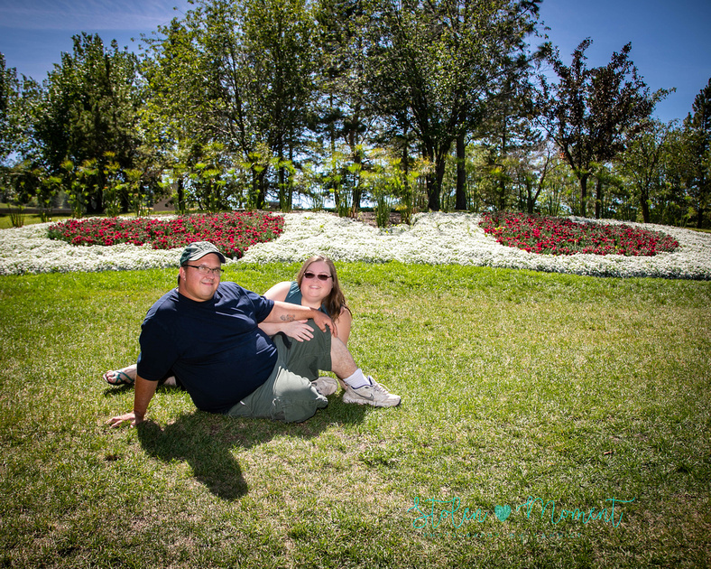 a couple sit on the grass in front of a flower bed shaped into two hearts at the grounds of the Muttart Conservatory, Edmonton