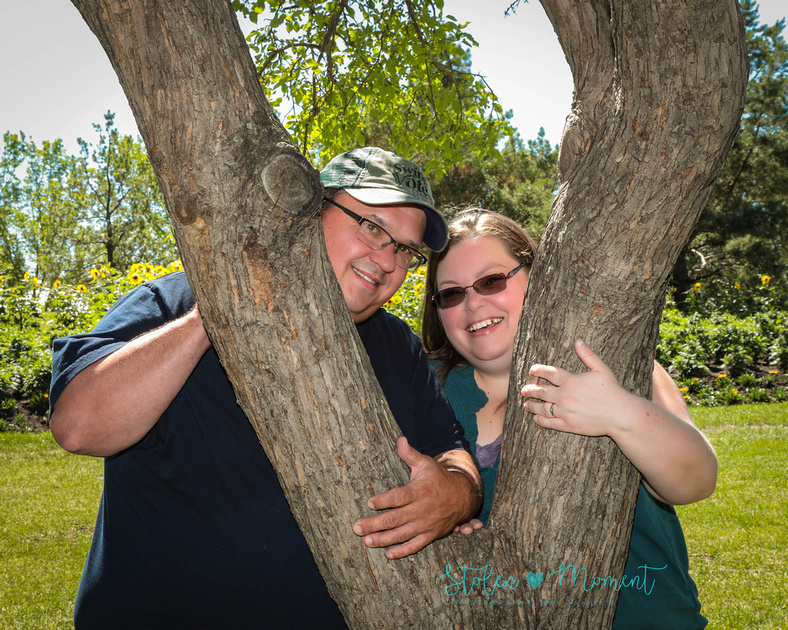 a woman and her fiancé peek in between branches of a tree smiling for camera