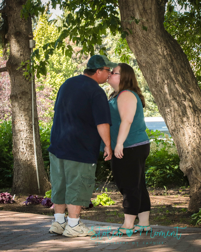 an engaged couple share a kiss on a pathway at the grounds of the Muttart conservatory