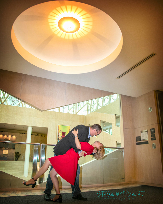 a man dips his fiancé in front of the railings on second floor of Edmonton city hall
